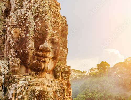 Wall mural Enigmatic giant stone face of Bayon temple in evening sun