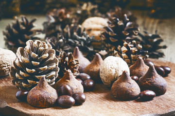 Fir cones, nuts, chocolate truffles and candy on the old wooden