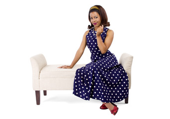 Woman wearing a blue ploka dot dress on a traditional chaise furniture