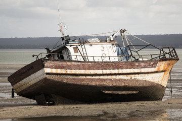 Old boat on the beach in low tide in Inhambane, Mozambique