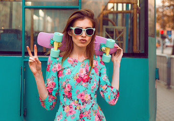 Beautiful and fashion young woman posing with a skateboard on