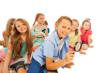 Boy searching with magnifying glass and friends