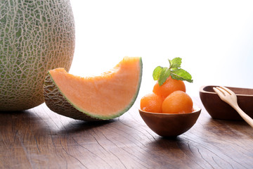 Organic cantaloupe melon in wooden spoon on wooden table