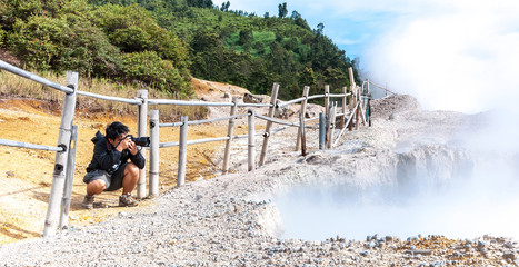 Nature photographer with digital camera take photo of Sulfur Mud