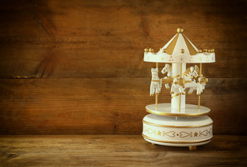 old vintage white carousel horses on wooden table. retro filtered image
