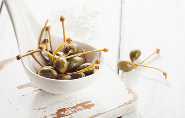 Pickled capers on a white spoon.