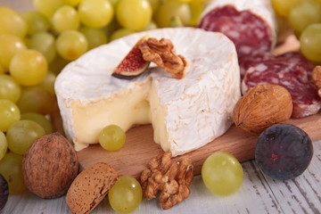 cheese with grape and nut on board