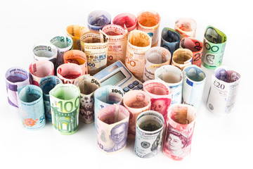 Pile of rolled-up currency notes with a calculator surrounded