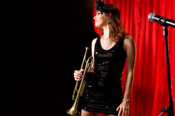 Woman on stage play on the trumpet.Red velvet curtain  on background