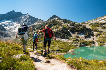 Foto op Canvas Alpen family with child hiking on holiday in austrian alps with lake and glacier view