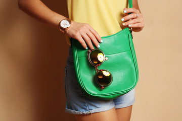 Wall Mural - Trendy girl with green handbag clutch and sunglasses