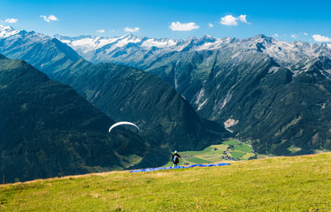 paraglider ready for start in austrian summer alps with epic view