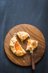 Homemade apricot pie on the wooden cutting board. Chalkboard background with copy space
