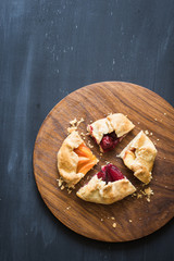 Assorted homemade pie pieces with pluots, apricots, sour cherries and flat peaches on the wooden cutting board. Chalkboard background with copy space