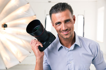 Handsome photographer holding camera