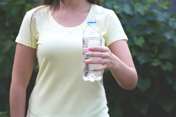 Plastic bottle of water in the hands of a girl