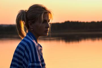 Женщина на берегу озера на закате