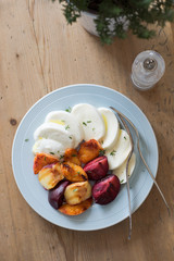 Starter of italian mozzarella cheese and grilled pluots, apricots and flat peaches with olive oil and thyme on the wooden background