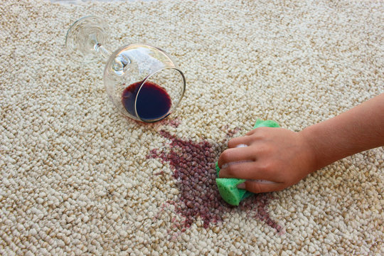 glass of red wine fell on carpet, wine spilled on carpet. Female hand cleans the carpet with a sponge and detergent.