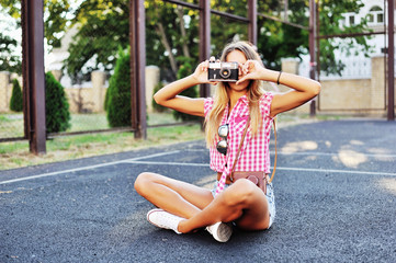 Stylish young woman using a camera to take photo outdoors