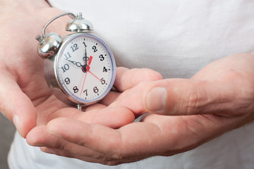Alarm Clock in male hands close-up
