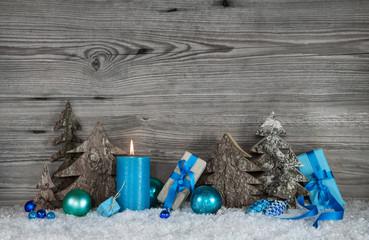 Dekoration zu Weihnachten in Blau mit Geschenke und Holz Hintergrund in Grau mit Schnee.