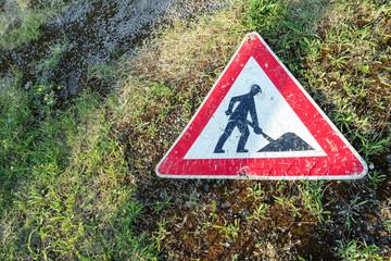"""Straßenschild """"Achtung Baustelle"""" auf dem Boden liegend"""