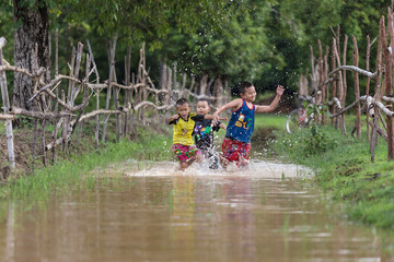 children playing on water in road