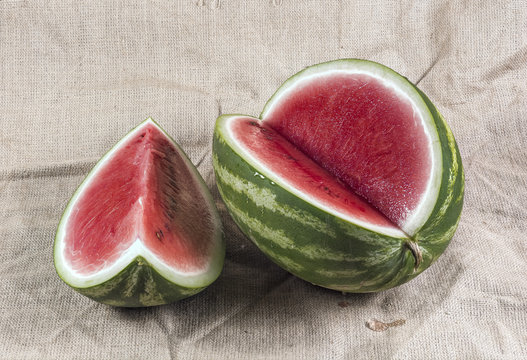 Ripe striped cut watermelon with water drops on a burlap canvas