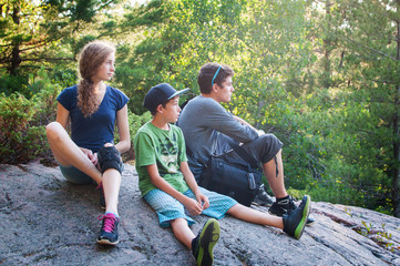 three siblings enjoying the view from atop a nature hike lookout