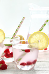 Raspberries and juice in glass on white wooden background