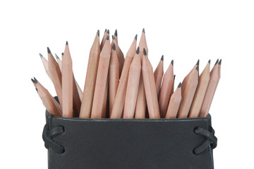 Stock picture of beige pencils in a black leather box, on white, isolated background