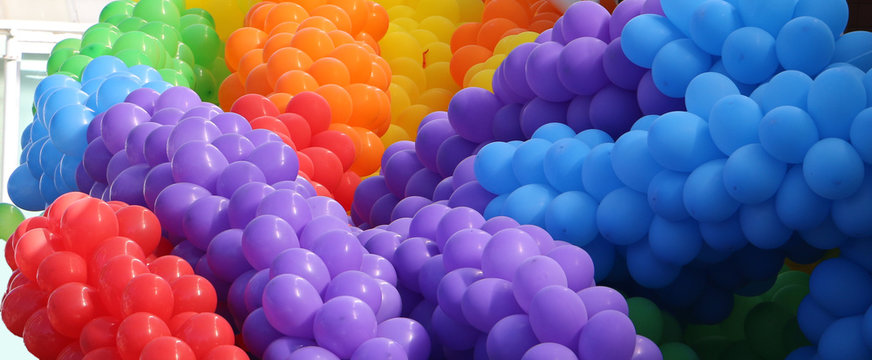 Groups of violet, blue, red, orange, yellow, green balloons together making cheerful colorful pile