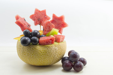 Healthy attractive fruit salad served in a fresh melon against b