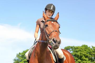 Teenage girl equestrian riding horseback. Vibrant summertime out