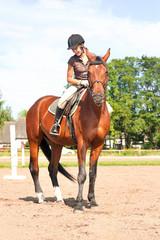 Teenage girl equestrian riding thoroughbred horseback. Vibrant summertime outdoors image.