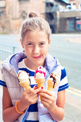 Happy smiling young cute girl with many ice-cream. Outdoors imag