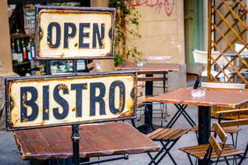 Open bistro sign at the empty caffe terrace