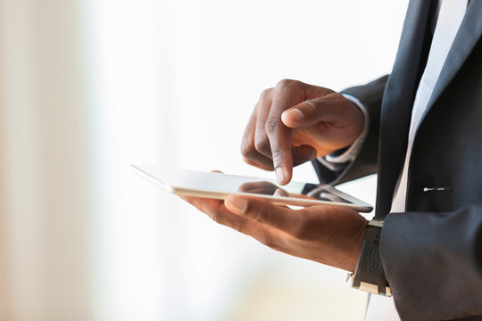 African american business man using a tactile tablet over white