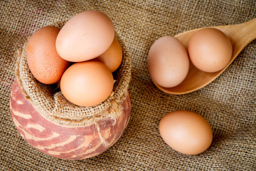 Fresh raw eggs in clay pot put on old sack