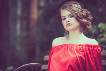 portrait of a beautiful young  girl in a red dress outdoors