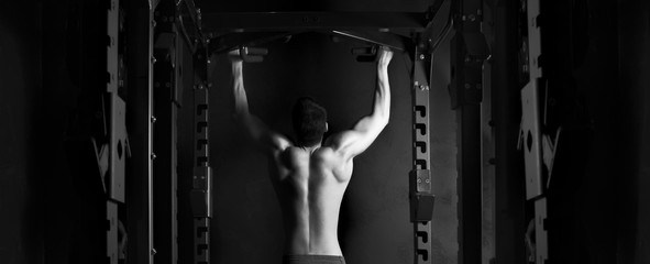 Muscle athlete man in gym making elevations. Bodybuilder training in gym .