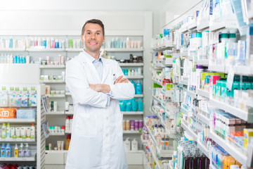 Smiling Pharmacist Standing Arms Crossed In Pharmacy