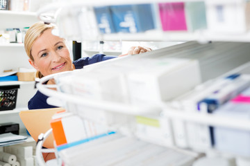 Female Chemist Counting Stock In Pharmacy