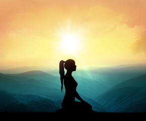 Yoga and meditation. Silhouette of woman in mountains.