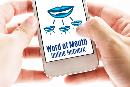 Close up Two hand holding smart phone with word of mouth online