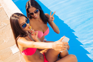 Two woman in swimsuit making selfie photo