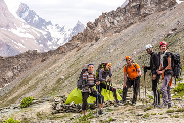 Alpine climbers team and camp Group of five people men and women staying along green camping tent on majestic mountain landscape of deserted Asian area