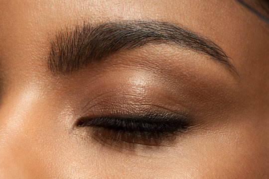 Close-up closed eye with make-up with brown eyebrows and black lashes