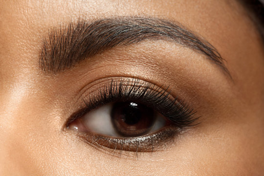 Close-up of make-up eye with long eyelashes and brown eyebrows of black woman